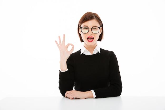 Szczęśliwa młoda biznesowa dama jest ubranym szkła pokazuje zadowalającego gest.