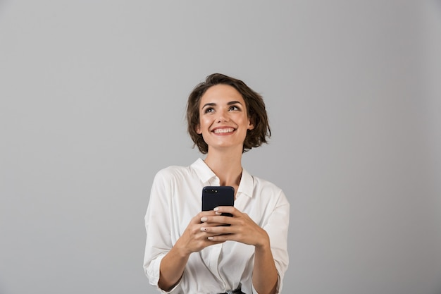 Szczęśliwa młoda biznesowa kobieta pozuje za pomocą telefonu komórkowego i na czacie