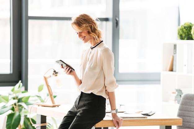 Szczęśliwa młoda biznesowa kobieta w biurze