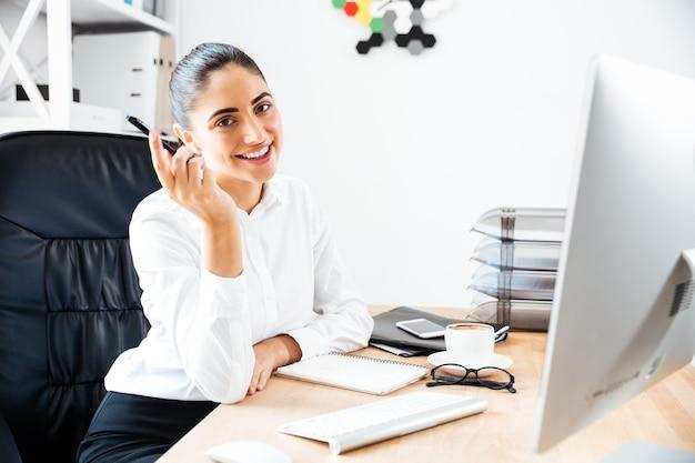 Szczęśliwa młoda bizneswoman siedzi w swoim miejscu pracy, trzymając długopis i patrząc na przód