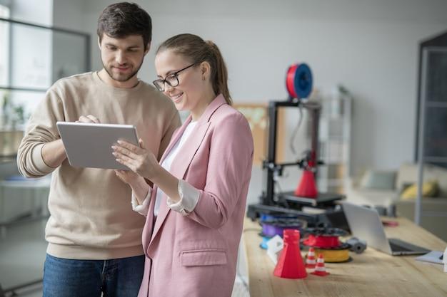 Szczęśliwa młoda bizneswoman trzyma touchpad, podczas gdy jej kolega dokonywanie prezentacji kreatywnych pomysłów lub szkiców elektronicznych