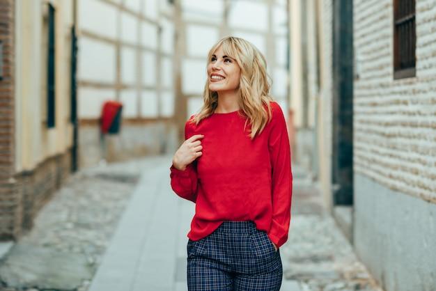 Szczęśliwa młoda blond kobieta idąc ulicą.