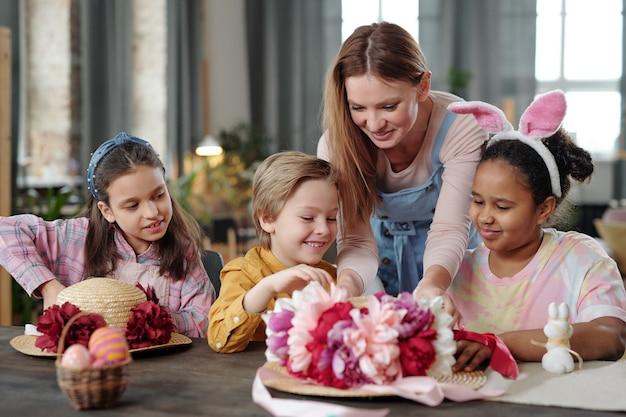 Szczęśliwa młoda blond kobieta pochyla się nad grupą dzieci, pomagając im przy dekorowaniu kapeluszy ręcznie robionymi kwiatami przy stole