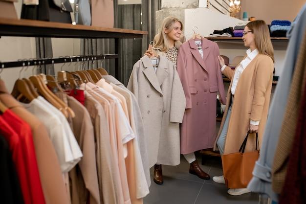 Szczęśliwa młoda blond kobieta pokazuje matce dwa eleganckie płaszcze z sezonowej kolekcji, wybierając nowe ubrania w centrum handlowym