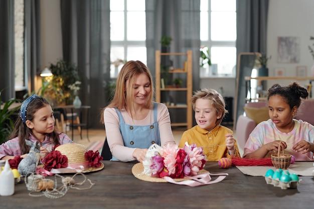 Szczęśliwa młoda blond kobieta pomaga uroczym małym dzieciom dekorować kapelusze ręcznie robionymi kwiatami o żywych kolorach, siedząc przy stole