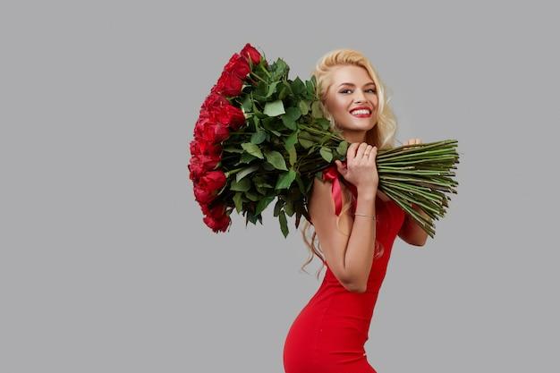 Szczęśliwa młoda blond kobieta trzyma duży bukiet czerwonych róż jako prezent na 8 marca lub walentynki.