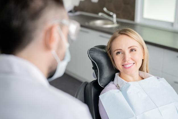 Szczęśliwa młoda blond pacjentka patrząc na swojego dentystę ze zdrowym uśmiechem siedząc w fotelu przed badaniem