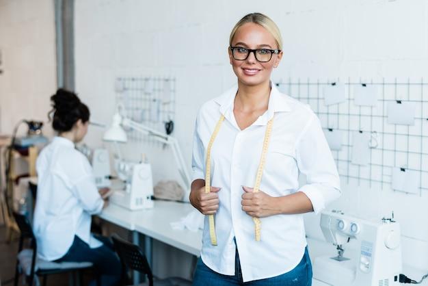 Szczęśliwa młoda blondynka krawcowa z miarką patrząc na ciebie stojąc w fabryce lub warsztacie z maszynami do szycia
