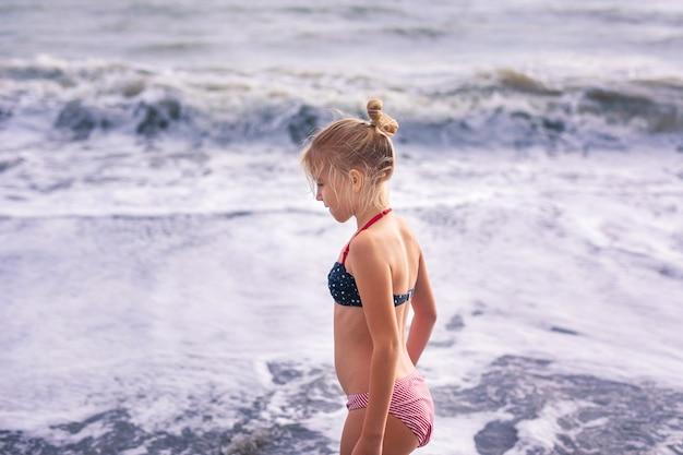 Szczęśliwa młoda blondynki dziewczyna ma zabawę przy wymarzoną plażą z dużymi białymi fala