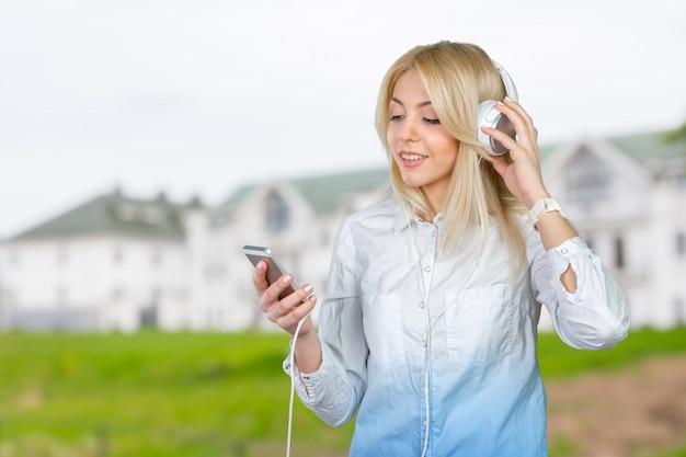 Szczęśliwa młoda blondynki kobieta słucha muzyka