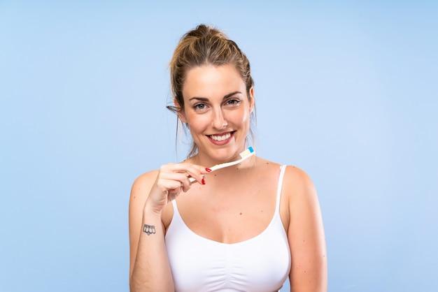Szczęśliwa młoda blondynki kobieta szczotkuje jej zęby