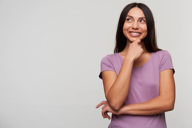 Szczęśliwa młoda brązowooka brunetka dama ubrana w fioletową koszulkę pokazująca swoje idealne białe zęby, uśmiechając się szeroko, patrząc rozmarzonym wzrokiem w górę, stojąc na białym