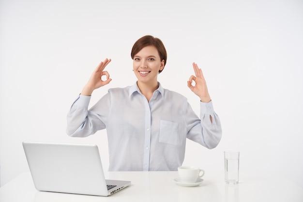 Szczęśliwa młoda brązowooka krótkowłosa brunetka dama z przypadkową fryzurą podnosząca ręce z ok gestem i wyglądająca pozytywnie z uroczym uśmiechem, odizolowana na białym
