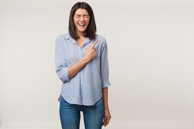 Szczęśliwa młoda brunetka kobieta z zamkniętymi oczami i głośno się śmiejąca, wskazując palcem wskazującym na prawą stronę na pustym miejscu, ubrana w pasiastą koszulę, na białym tle