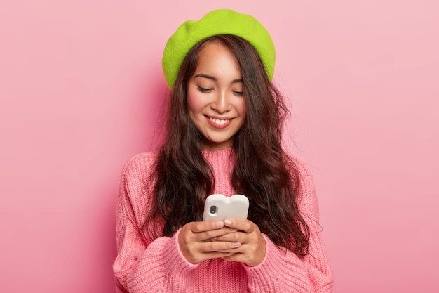 Szczęśliwa młoda brunetka koreanka trzyma nowoczesny telefon komórkowy, wysyła swoje zdjęcie do chłopaka, czyta zabawne powiadomienie