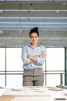 Szczęśliwa młoda brunetka projektantka mody skrzyżowana ramionami przy piersi, stojąc przy biurku przed kamerą