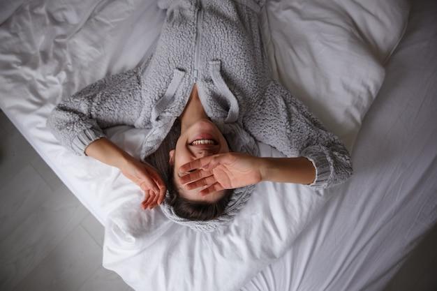 Szczęśliwa młoda brunetka wygrzewa się w łóżku wczesnym rankiem, leży na białej pościeli i trzyma ręce na twarzy, uśmiecha się radośnie i jest w dobrym nastroju