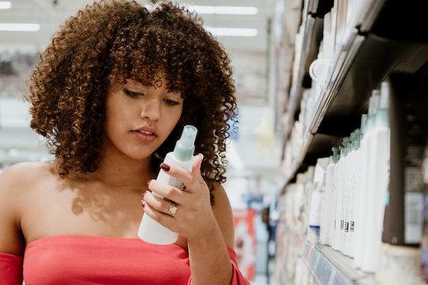 Szczęśliwa młoda brunetka z kędzierzawego włosy kupienia szamponem w supermarkecie