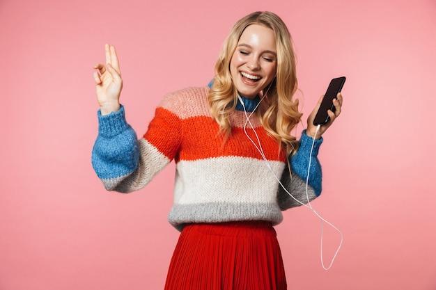 Szczęśliwa młoda całkiem piękna kobieta pozuje na białym tle nad różową ścianą za pomocą telefonu komórkowego słuchania muzyki przez słuchawki