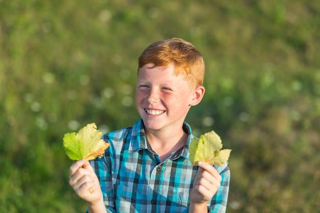 Szczęśliwa młoda chłopiec trzyma jesień liście