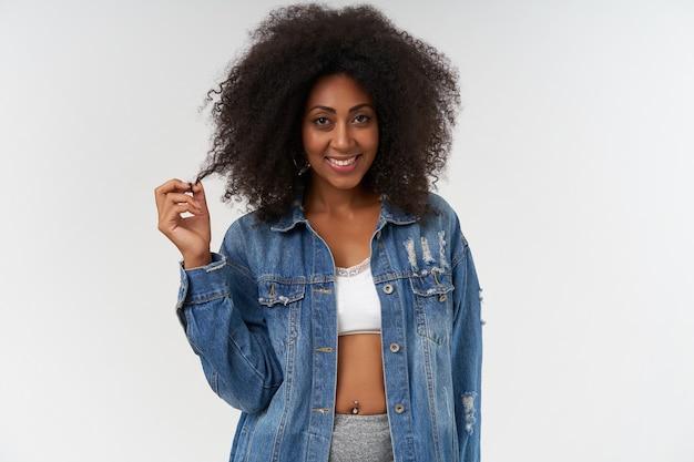 Szczęśliwa młoda ciemnoskóra dama w zwykłych ubraniach, ciągnąca kręcone włosy, stojąca nad białą ścianą, z uroczym pozytywnym uśmiechem