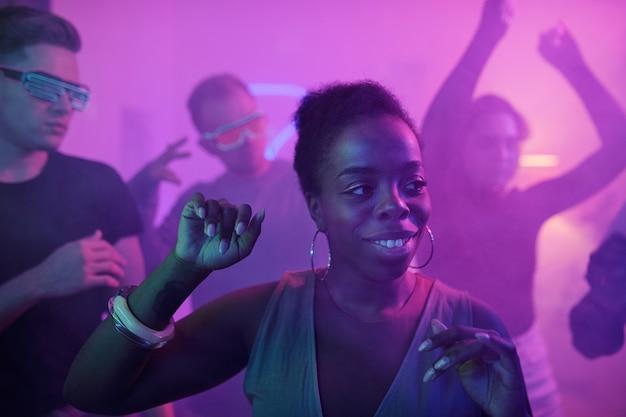 Szczęśliwa młoda czarująca kobieta pochodzenia afrykańskiego w eleganckiej sukience patrząc na bok podczas tańca przed kamerą wśród przyjaciół na imprezie domowej