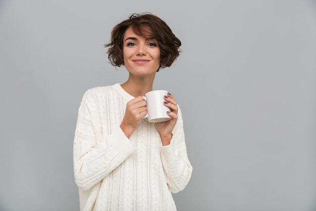 Szczęśliwa młoda dama pije herbaty.