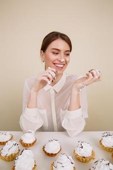 Szczęśliwa młoda dama pozuje podczas gdy jedzący babeczki.