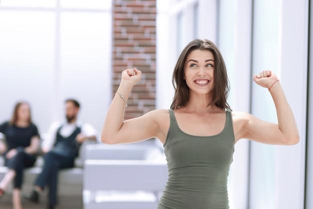 Szczęśliwa młoda dama stojąca w banku office.photo z miejscem na kopię