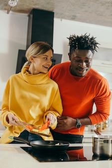 Szczęśliwa młoda dama uśmiechając się i patrząc na swojego chłopaka, stojąc z deską do krojenia i warzywami na to