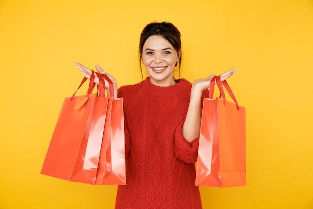 Szczęśliwa młoda dama w czerwonym swetrze z torby na zakupy w żółtym studio.
