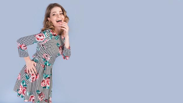 Szczęśliwa młoda dama w eleganckiej sukni z ręką na biodrze