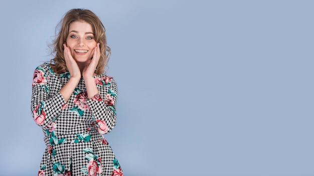 Szczęśliwa młoda dama w eleganckiej sukni z rękami na twarzy