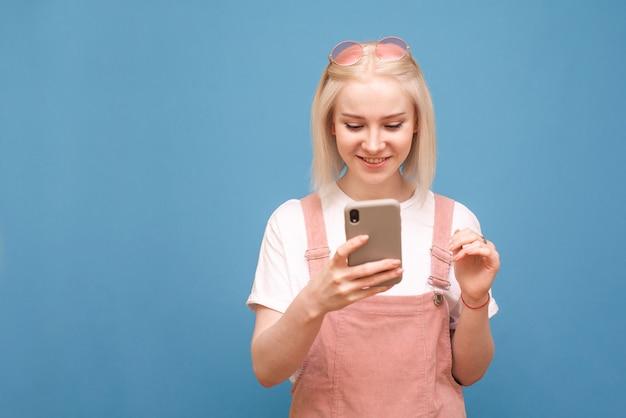 Szczęśliwa młoda dama w uroczych ubraniach stojących na niebieskim tle, za pomocą smartfona i uśmiechnięta, ubrana w okulary przeciwsłoneczne, białą koszulkę i różową sukienkę