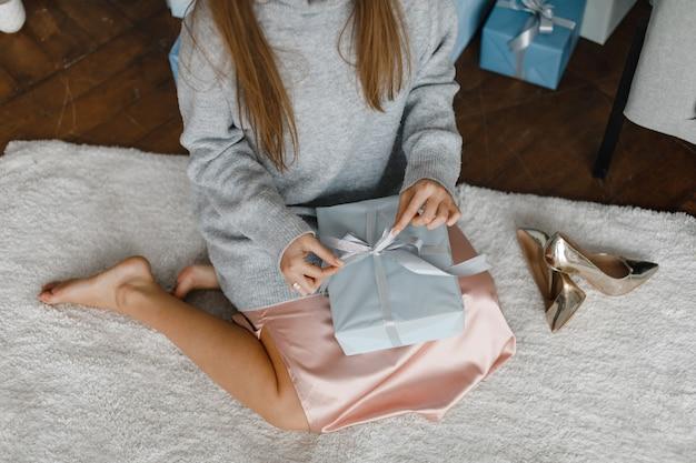 Szczęśliwa młoda dama z prezentami w pobliżu choinki. koncepcja nowego roku.