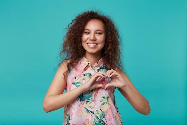 Szczęśliwa młoda długowłosy kręcone kobieta z naturalnym makijażem tworząc serce z uniesionymi rękami i uśmiechając się radośnie, stwarzając na niebiesko