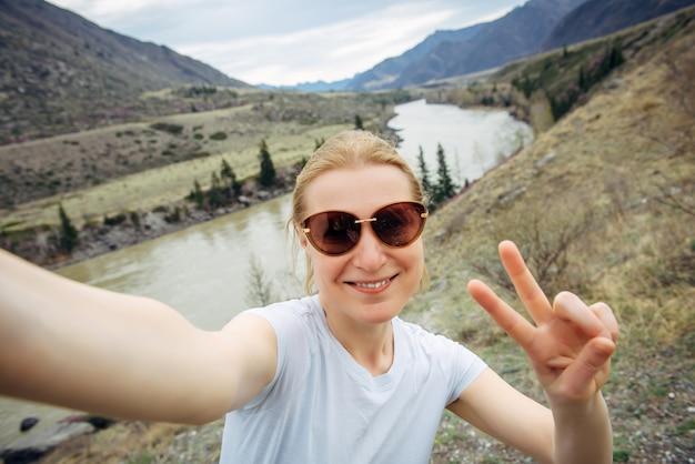 Szczęśliwa młoda dorosła kobieta w okularach przeciwsłonecznych ma selfie, śmiejąc się do kamery. podróże, blogowanie