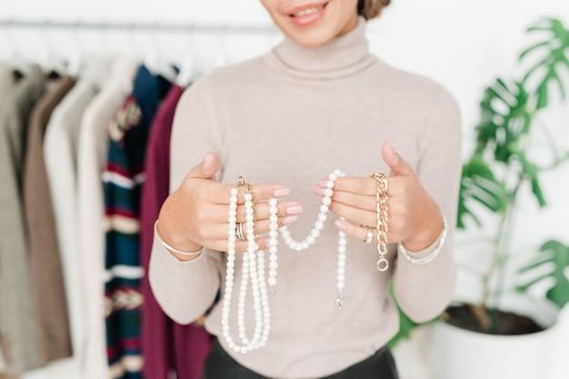 Szczęśliwa młoda dorywczo kobieta pokazująca perłowe akcesoria i bransoletkę ze złotego łańcucha, wybierając jedną z nowej kolekcji