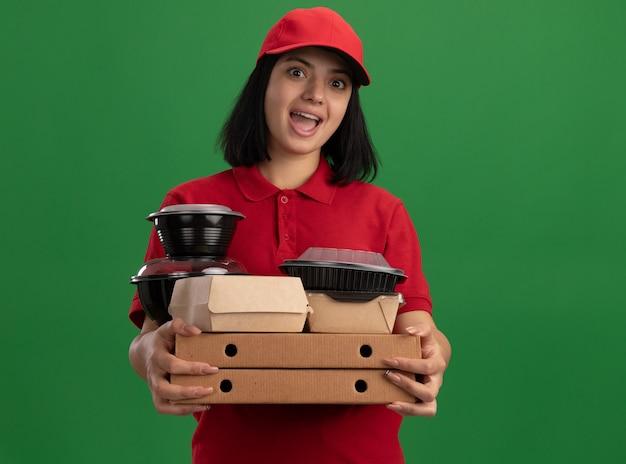 Szczęśliwa młoda dostawa dziewczyna w czerwonym mundurze i czapce trzymająca pudełka po pizzy i paczki z jedzeniem zaskoczona stojąc nad zieloną ścianą