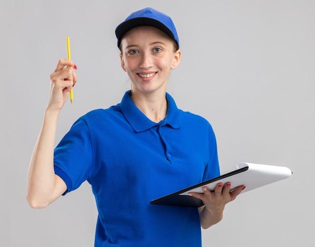 Szczęśliwa młoda dostawa dziewczyna w niebieskim mundurze i czapce, trzymająca ołówek i schowek z pustymi stronami, uśmiechając się pewnie stojąc nad białą ścianą