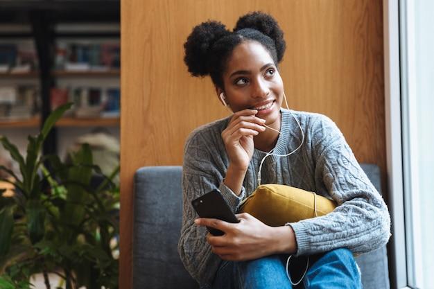 Szczęśliwa młoda dziewczyna afrykańskiego studenta studiuje w bibliotece, słuchając muzyki przez słuchawki