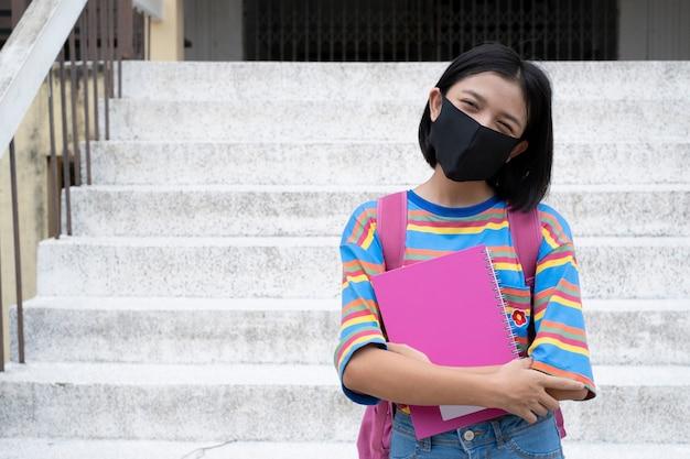 Szczęśliwa młoda dziewczyna azjatyckich nosić maskę i trzymać książkę w szkole