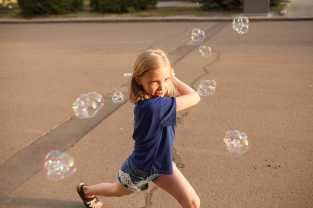 Szczęśliwa młoda dziewczyna bawi się, biegając dookoła, dmuchając bańki mydlane na zewnątrz