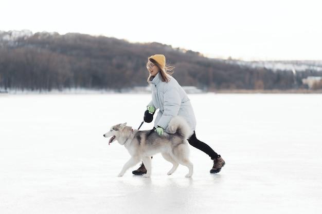 Szczęśliwa młoda dziewczyna bawić się z siberian husky psem w zima parku