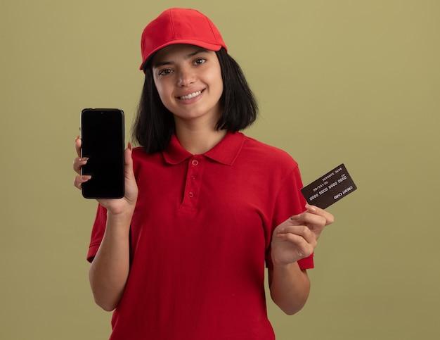 Szczęśliwa młoda dziewczyna dostawy w czerwonym mundurze i czapce przedstawiająca smartphine i kartę kredytową, uśmiechając się wesoło, stojąc nad zieloną ścianą
