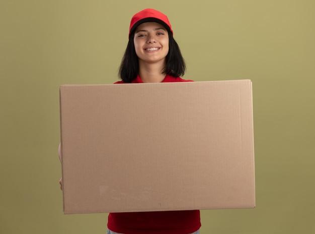 Szczęśliwa młoda dziewczyna dostawy w czerwonym mundurze i czapce trzyma duży karton z uśmiechem na twarzy stojącej nad jasną ścianą