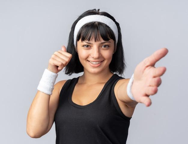 Szczęśliwa młoda dziewczyna fitness nosi opaskę, patrząc na kamery, uśmiechając się, pokazując kciuki do góry, dzięki czemu przyjdź tutaj gest ręką