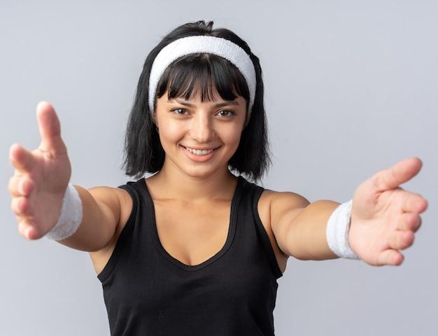 Szczęśliwa młoda dziewczyna fitness nosi opaskę, patrząc na kamery, uśmiechając się przyjazny, robiąc powitalny gest szeroko otwierając ręce stojąc na białym tle