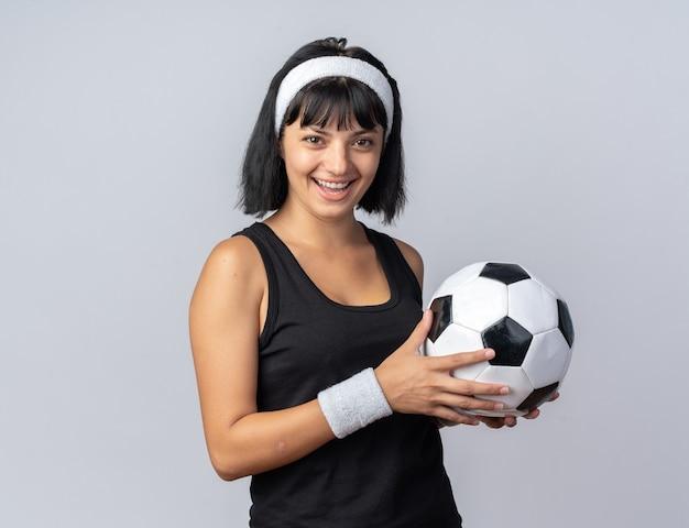 Szczęśliwa młoda dziewczyna fitness nosząca opaskę, trzymająca piłkę nożną, patrząc na kamerę, uśmiechając się radośnie