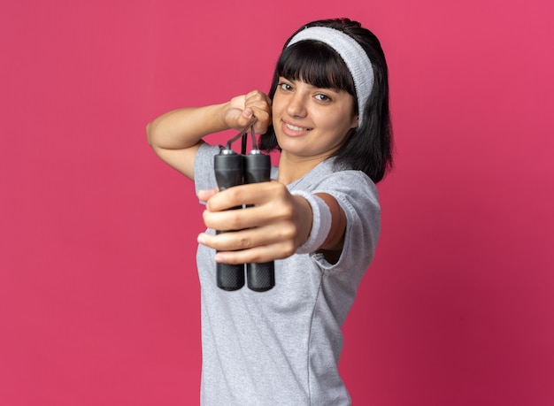 Szczęśliwa młoda dziewczyna fitness nosząca opaskę trzymającą skakankę patrzącą na kamerę z uśmiechem na twarzy stojącej na różowym tle